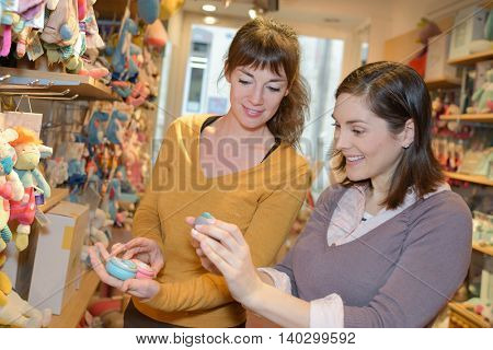 female friends in toy store shopping for their kids