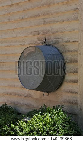 A large metal wash tub hanging on the outside of a house