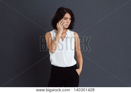 Confused young woman talking on her phone over grey background