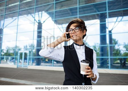 Young successful businesswoman in glasses speaking on phone, smiling, holding coffee, standing near business centre.