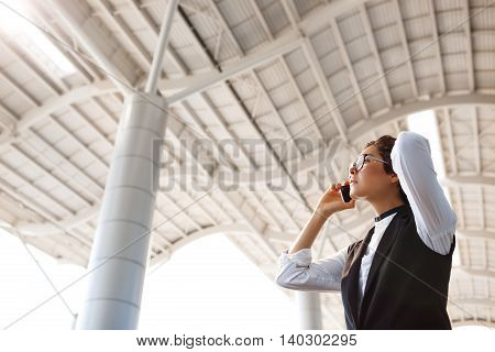 Young successful businesswoman in glasses speaking on phone, holding coffee, standing near business centre.