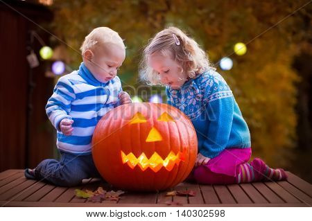 Little girl and boy carving pumpkin at Halloween. Dressed up children trick or treating. Kids trick or treat. Child in witch costume playing in autumn park. Toddler kid with jack-o-lantern.