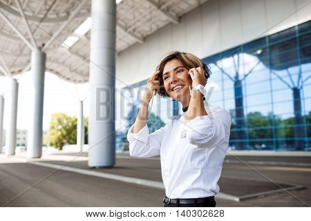 Young successful businesswoman speaking on phone, holding tablet, smiling, standing near business centre.