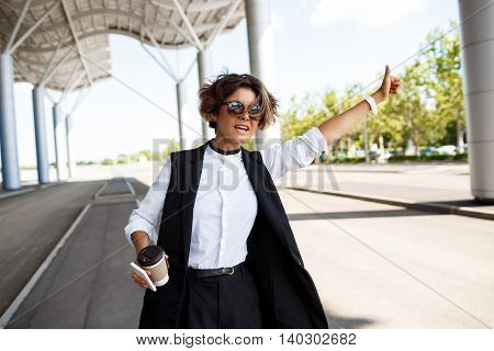 Young successful businesswoman in sunglasses holding coffee and phone, catching car over business centre.