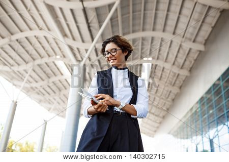 Young successful businesswoman in glasses looking at tablet, smiling, standing near business centre.