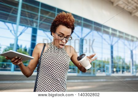 Young successful african businesswoman in glasses drenched with coffee standing near business centre.