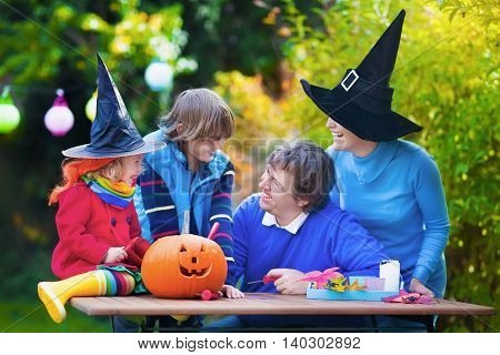 Family carving pumpkin at Halloween. Dressed up child trick or treating. Kids and parents trick or treat. Child in witch costume playing in autumn park. Toddler kid with jack-o-lantern.
