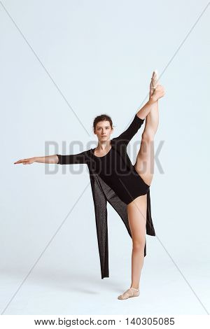 Young beautiful contemporary brunette dancer looking at camera, posing over white background. Copy space.