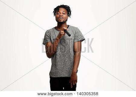 Young handsome african man looking at camera, singing in microphone over white background. Copy space.