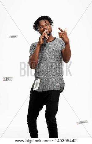 Young handsome african man winking, singing in microphone over white background. Copy space.