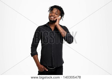 Young successful african businessman in black shirt speaking on phone, smiling over white background. Copy space.