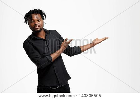Young successful african businessman in black shirt pointing hands in side, looking at camera over white background. Copy space.