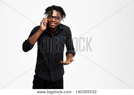 Young successful african businessman in black shirt and glasses speaking on phone, smiling, looking at camera over white background. Copy space.