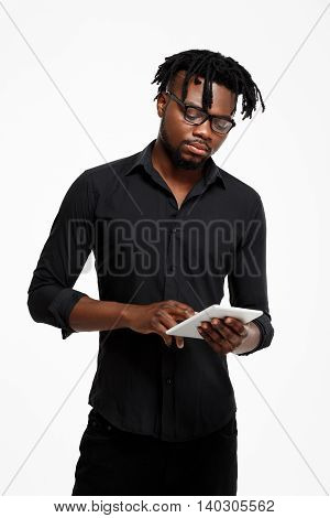Young successful african businessman in black shirt and glasses holding tablet, looking at screen over white background.