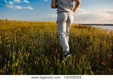 Close up photo of young sportive man jogging in field at sunrise.