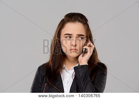 Upset young beautiful girl speaking on phone over purple background. Copy space.