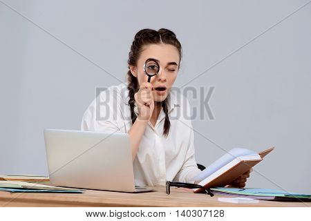 Young beautiful businesswoman sitting at workplace, holding book, looking at camera through magnifier over purple background. Copy space.