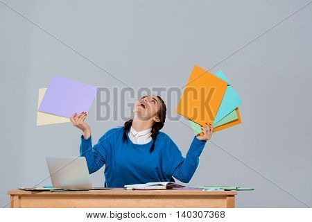 Young beautiful businesswoman sitting at workplace, holding colorful folders, looking up over purple background. Copy space.
