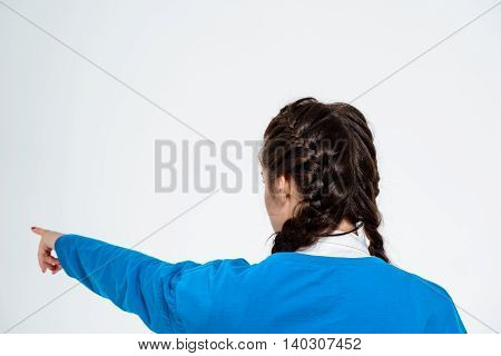 Young beautiful girl standing back to camera, pointing finger away over white background. Copy space.