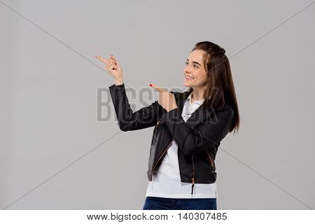 Young beautiful girl pointing fingers in side, smiling over purple background. Copy space.