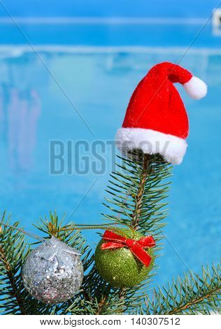 Santa Claus hat on a branch of spruce and toys opposite the pool