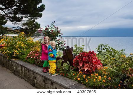 Cute little girl and boy walking down lakeside promenade in Montreux city center on cold autumn day. Children during fall vacation in Switzerland Geneva Lake. Traveling and tourism with kids.