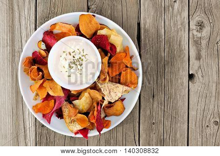Plate Of Mixed Healthy Vegetable Chips With Dip Overhead View On A Rustic Wood Background