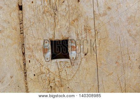 hole in the board of the old weathered gray wood