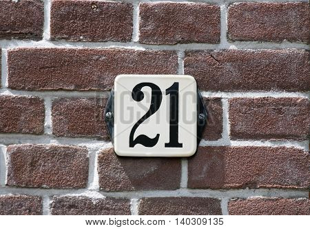 Enameled house number twenty one on a red brick wall