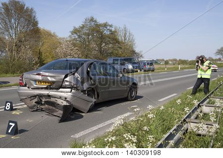 Bovenkarspel, the Netherlands - May 5, 2016: Police taking pictures, pictures of a damaged car after an accident. An accident in the road-which is turned off for a few hours.