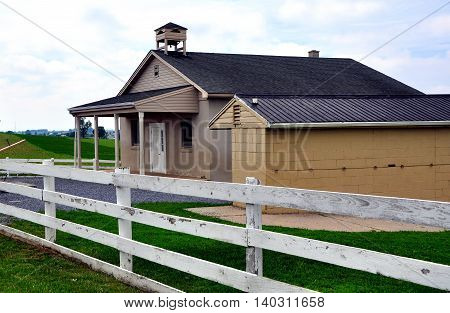 Lancaster County Pennsylvania - June 6 2015: A one-room Amish school house and buggy shed set amidst rolling farmlands on a country road