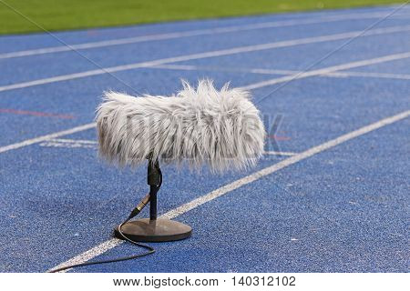 Big and furry professional sport microphone near the football field