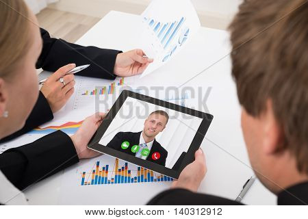 Close-up Of Businesspeople Video Conferencing On Digital Tablet In Office