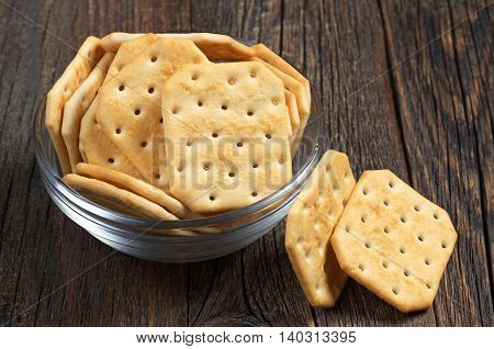 Square crackers in glass bowl on dark wooden background