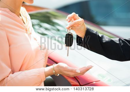 Close-up Of A Dealer Giving Car Key To Woman