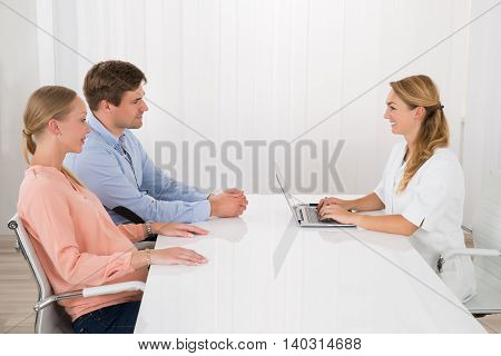 Female Doctor Using Laptop While Talking With Young Couple