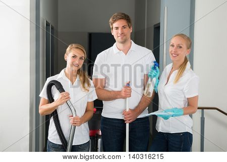 Group Of Happy Young Janitors Holding Cleaning Equipments