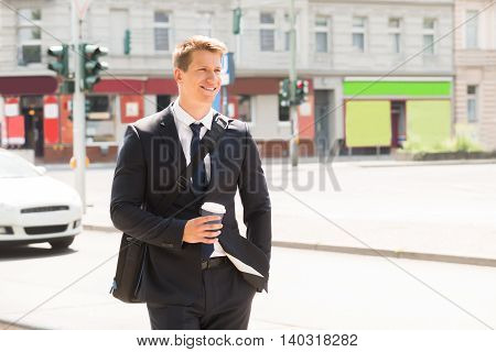 Smiling Young Man Walking On Street Holding Coffee Cup