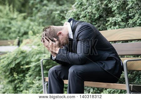 Photo Upset Young Businessman Sitting On Bench