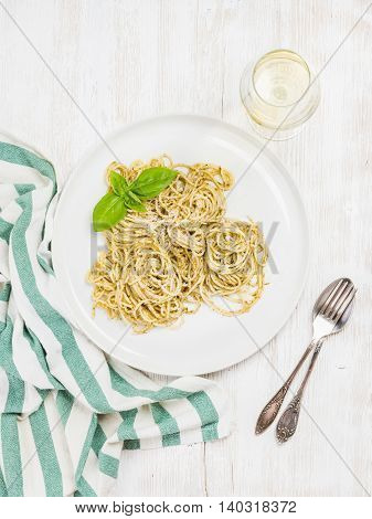 Pasta spaghetti with Pesto sauce and fresh basil, glass of white wine. White wooden painted background, top view, vertical composition
