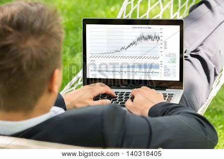 Close-up Of Male Stock Broker Lying In Hammock Using Laptop