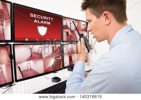 Young Male Security Guard Using Walkie-talkie While Looking At CCTV Footage On Multiple Computers