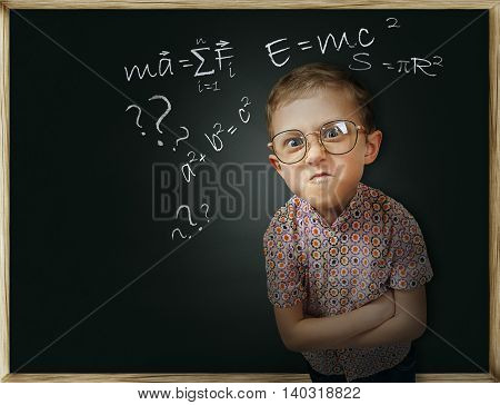 Frowning pupil boy near chalkboard having problems with physics