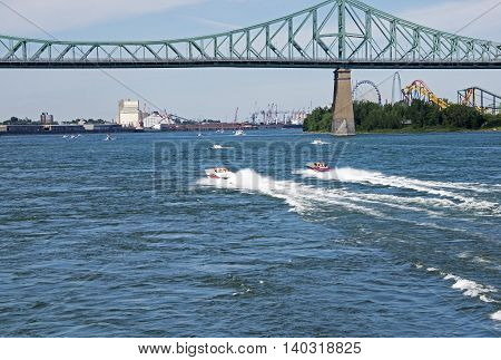 Power boats speeding towards the Jacques Cartier bridge in Montreal Quebec Canada