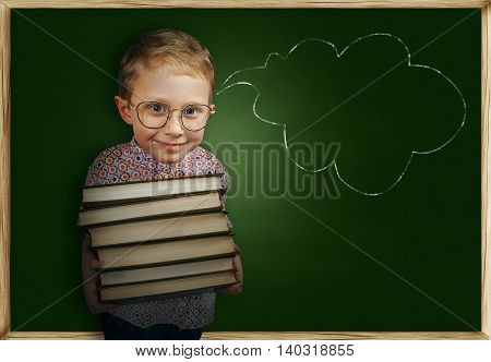 Bespectacled boy with books near school chalkboard