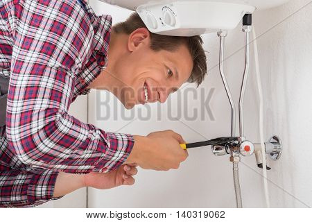 Happy Young Male Worker Repairing Electric Boiler With Wrench
