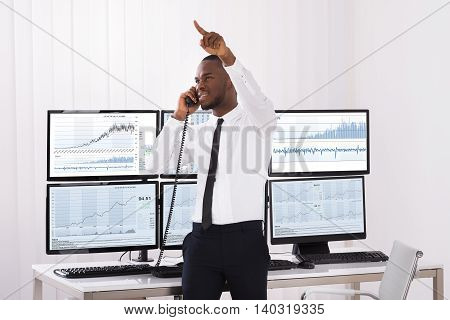 Male Stock Trader Pointing Upwards While Talking On Telephone