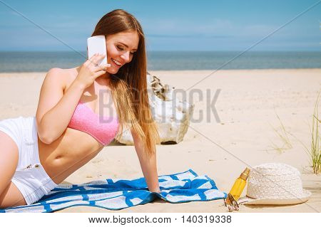 Technology and communication. Happy smiling woman with mobile phone calling to people friends. Young attractive girl talking by smartphone on beach.