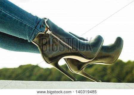 Autumn fashion outfit. Fashionable woman long legs in denim pants black stylish high heels shoes outdoor on city street