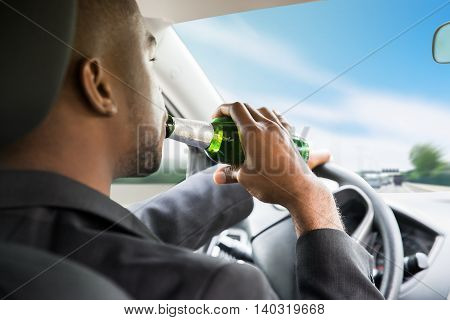 Side View Of A Young African Businessman Drinking Beer While Driving Car
